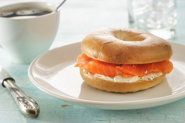 Bagel with salmon and cream chees on white plate