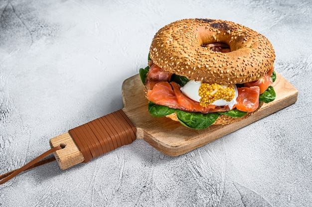 Bagel with salted salmon, cream cheese, avocado and egg. gray surface. top view