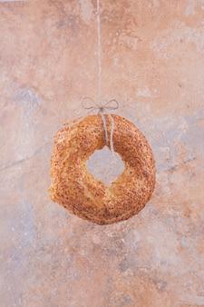Un bagel con sesamo su superficie di marmo