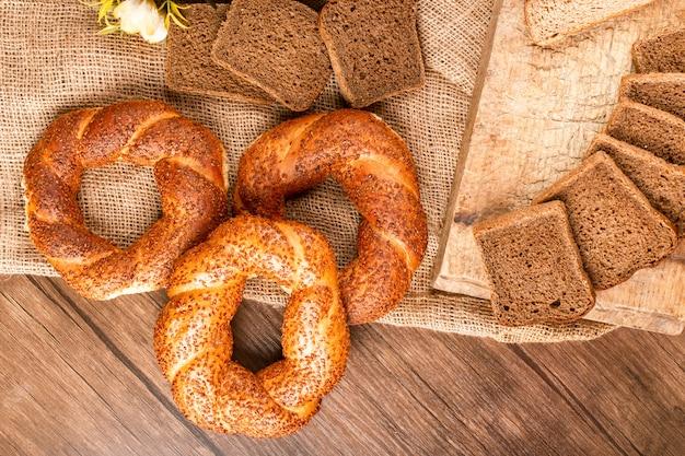 バスケットとテーブルクロスの上にベーグルとパンのスライス