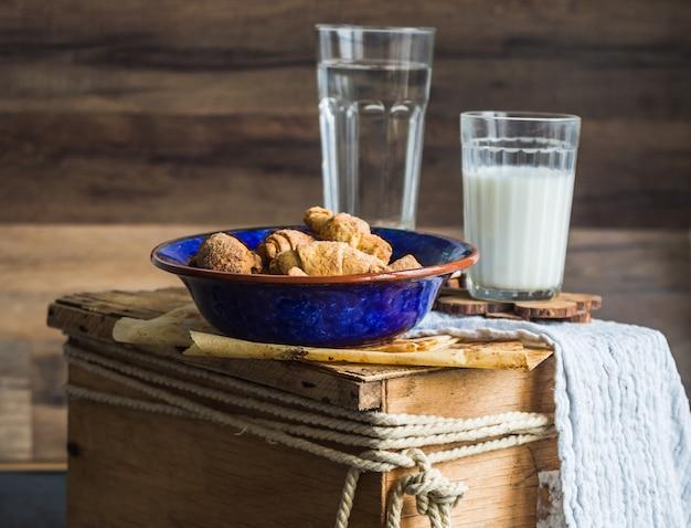 ショートペストリーのベーグルビスケット、フィリング、牛乳、青いプレートの甘いペストリー、木製