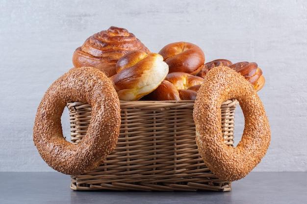 Bagel appesi a un cesto pieno di panini dolci su fondo marmo. foto di alta qualità