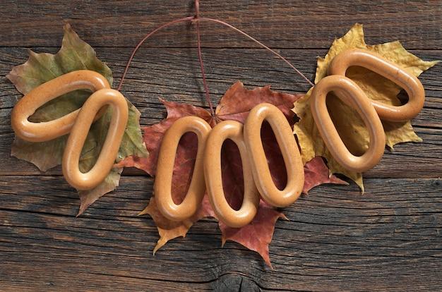 Бублики на старом деревянном столе с осенними листьями