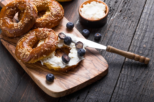 Bagels sandwich with cream cheese and on blueberry on wooden table