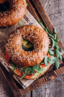 Bagels with cream, avocado, tomatos and arugula on wooden board.