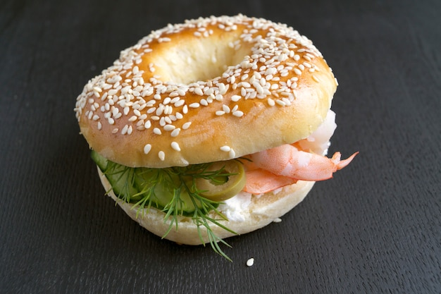 Bagels with cream cheese and shrimp on a black background