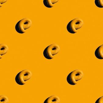 明るいオレンジ色の背景、コピースペース、フラットレイにケシの実のベーグル