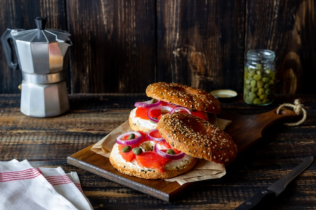 Рогалики с лососем, белым плавленым сыром и каперсами на деревянном фоне. рецепты. здоровое питание.