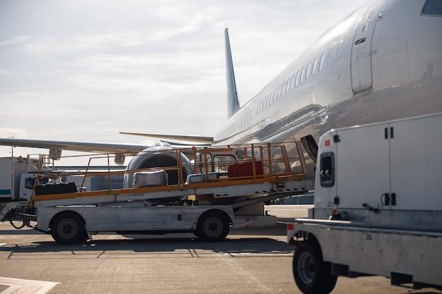 낮에 야외에서 비행기에서 내리는 컨베이어 벨트에 있는 수하물. 비행기, 운송, 운송 개념