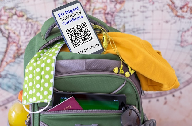 Baggage ready for travel, smartphone with european digital covid certificate por people vaccinated