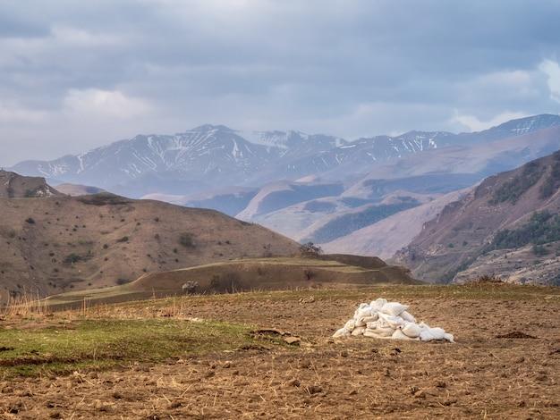 フィールド上の肥料の袋。山岳農業。