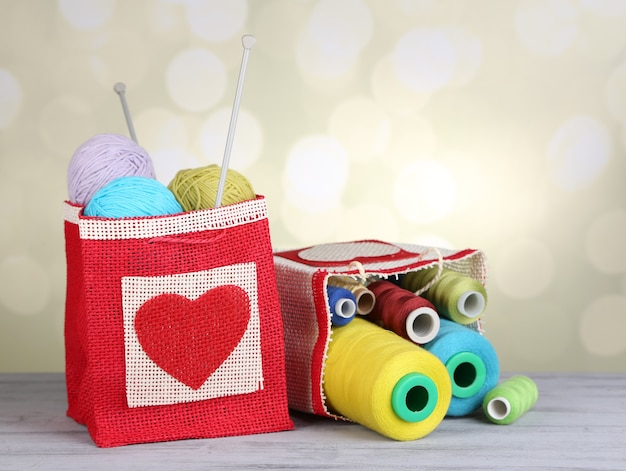 Bags with bobbins of colorful thread and woolen balls on wooden table, on light background