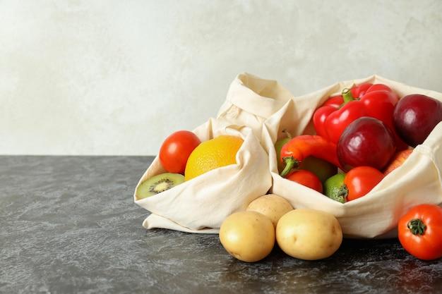 검은 스모키 테이블에 야채와 과일이 든 가방