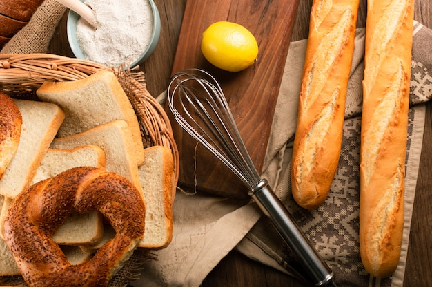 Baguette and bagels in basket with lemon and flour