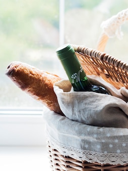 Baguette and bottle of wine in vintage wicker basket on window sil sill with green plants