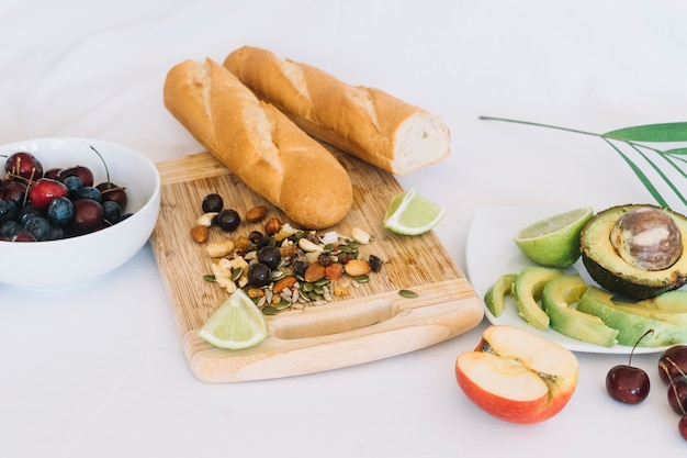 Baguette bread; dry fruits and fruits on white background