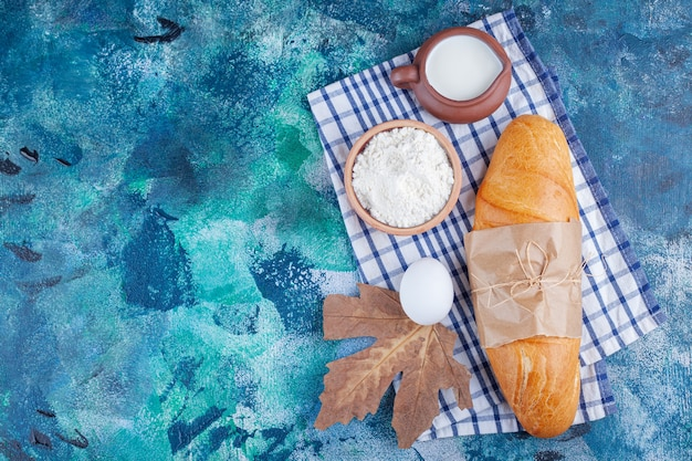 Baguette bread, flour, egg and milk on a tea towel , on the blue background.