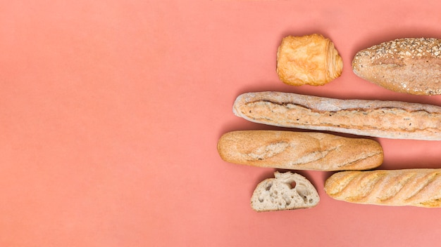 Baguette bread; loaf; puff pastry buns on colored background