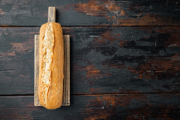Baguette bread, on old dark  wooden table table, top view flat lay
