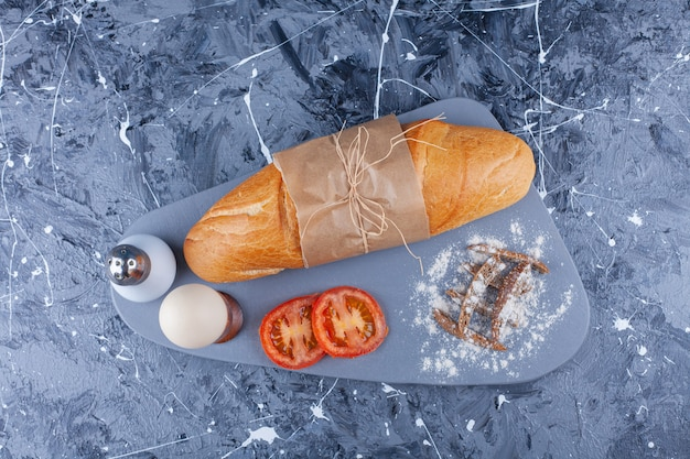 Багетный хлеб, нарезанные овощи, вареное яйцо на доске на синем.