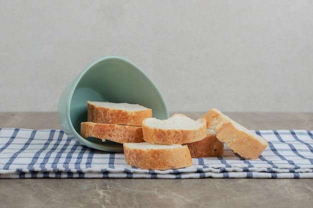 Fette di pane baguette dalla ciotola sulla tovaglia. foto di alta qualità