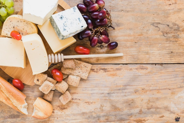 Baguette, cheese blocks with honey dripper, tomatoes and grapes on wooden desk