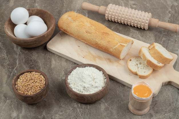 大理石の表面にバゲット、卵、小麦粉、大麦、麺棒。高品質の写真