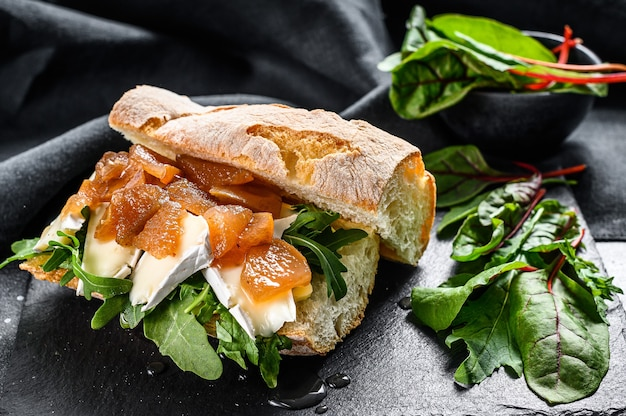 Baguette sandwich with goat cheese, pear marmalade, chard and spinach. black background. top view.
