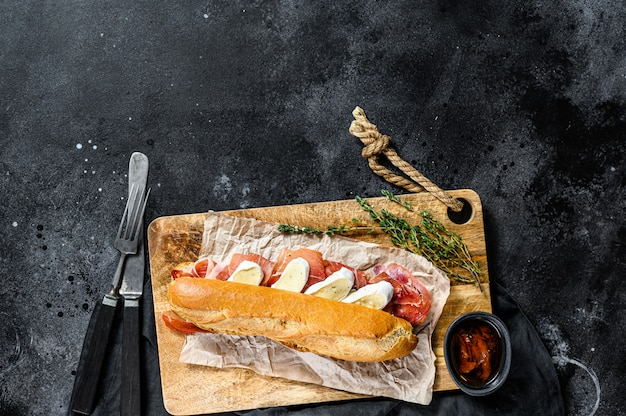 Baguette sandwich with jamon ham serrano, paleta iberica, camembert cheese on the cutting board.  black background, top view, space for text