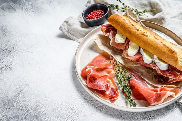 Baguette sandwich with jamon ham serrano, paleta iberica, camembert cheese on the cutting board.  gray background, top view, space for text
