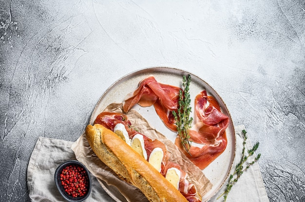Baguette sandwich with jamon ham serrano, paleta iberica, camembert cheese on the cutting board.  gray surface, top view, space for text