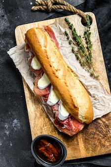 Baguette sandwich with jamon ham serrano, paleta iberica, camembert cheese on the cutting board.