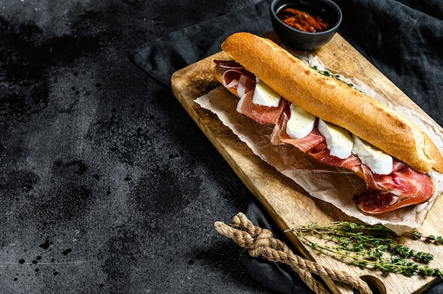 Baguette sandwich with jamon ham serrano, paleta iberica, camembert cheese on the cutting board