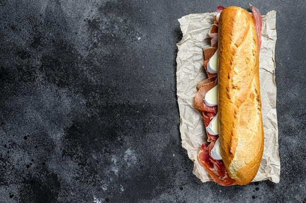 Baguette sandwich with jamon ham serrano, paleta iberica, camembert cheese. , top view