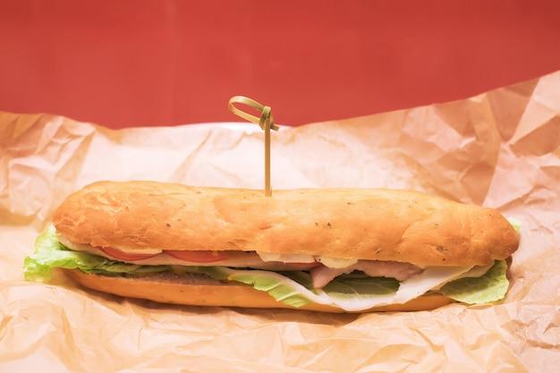 Багетный бутерброд с салатом, томатной колбасой и сыром