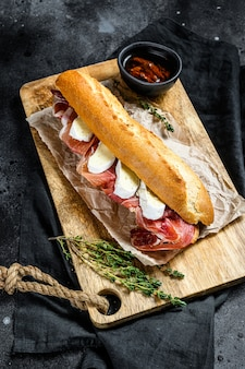 Baguette sandwich with prosciutto ham, camembert cheese on a cutting board. black background, top view.