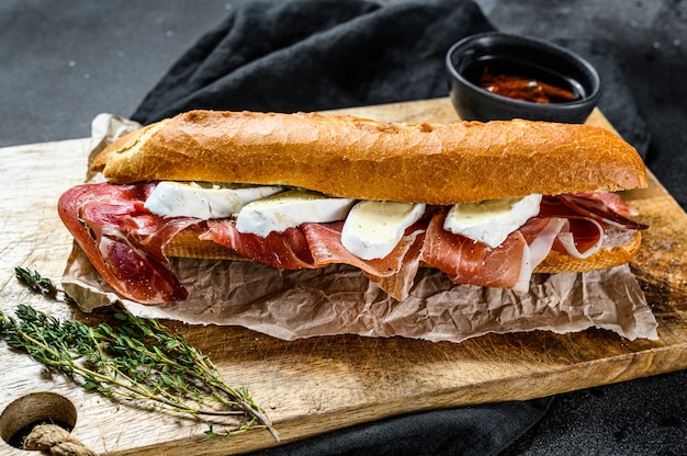 Baguette sandwich with prosciutto ham, camembert cheese on a cutting board.