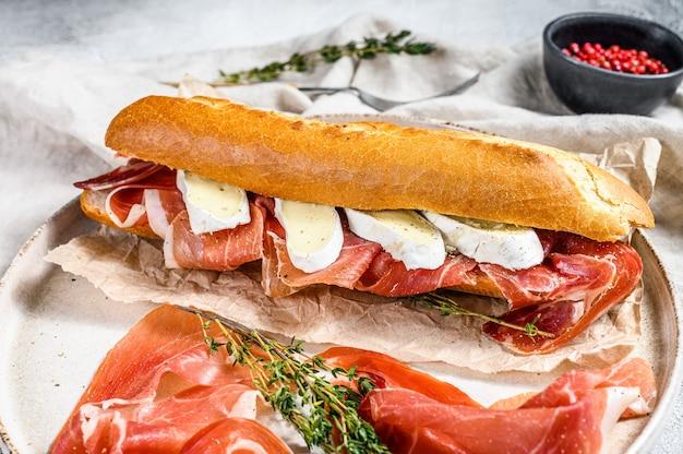 Багет бутерброд с ветчиной прошутто, сыр камамбер на тарелку. серая поверхность, вид сверху.
