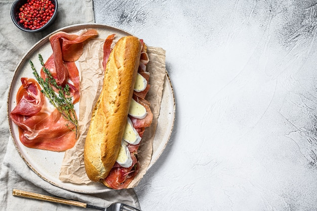 Baguette sandwich with prosciutto ham, camembert cheese on a plate.