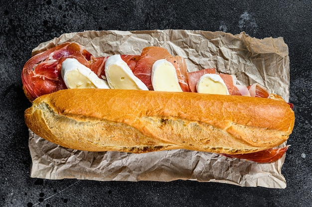 Baguette sandwich with prosciutto ham, camembert cheese