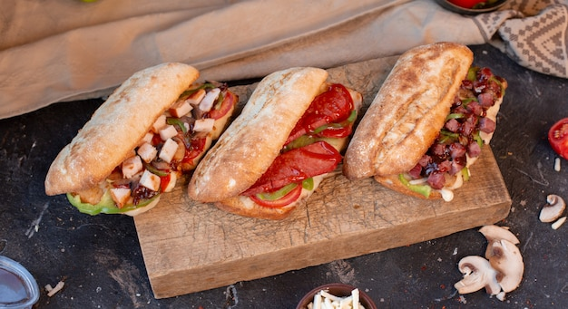 Baguette sandwiches with chicken, meat, sausage and vegetables, top view