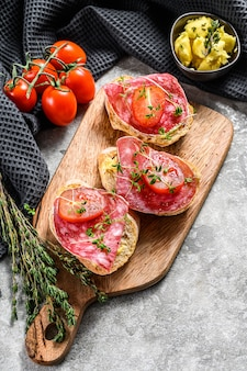 Baguette slices with salami and cherry tomatoes