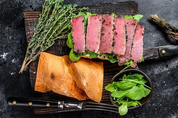 Багет сэндвич из стейка тунца с рукколой на разделочной доске. черный фон. вид сверху.