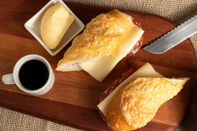 Baguette with cheese and salami served with a cup of coffee.