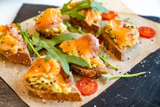 サーモンのバゲット。便利なビュッフェフィード。お祭りで小さなサンドイッチ。ケータリング。調理済みの食事の配達と宴会のサービス。
