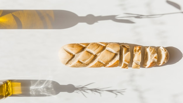 Baguette with shadow of olive bottles on backdrop