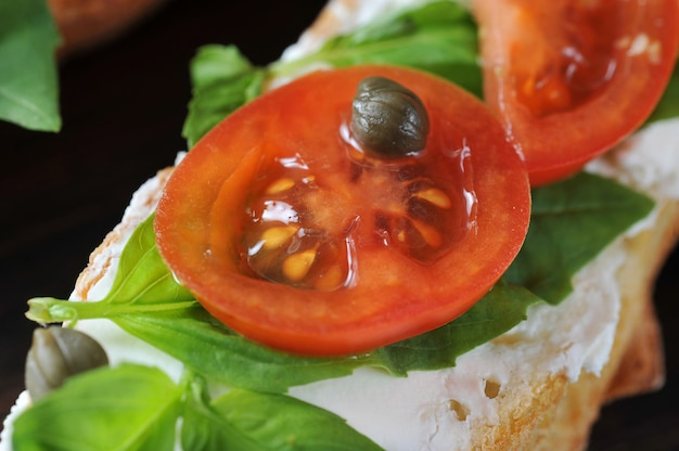 Baguette with soft cheese, basil, cherry tomatoes, capers