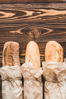 Baguettes in parchment on wooden table