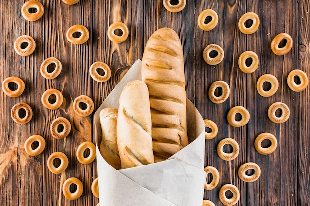 Baguettes wrapped in paper surrounded with bagels on wooden background