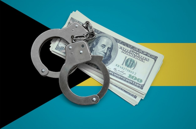 Bahamas flag  with handcuffs and a bundle of dollars. currency corruption in the country. financial crimes